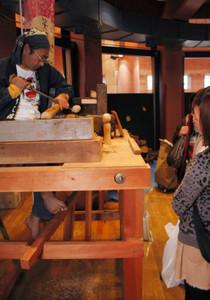 足でろくろを回しながら、木を削っていく早坂さん(左)=県こどもみらい館で