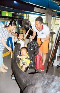 恐竜のオブジェに触れる親子=浜松市中区の浜松科学館で