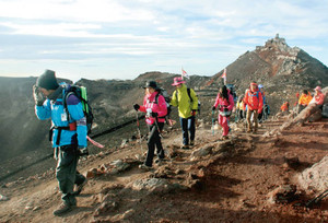 富士山頂で早朝の光を浴びながら「お鉢巡り」をする登山者=21日午前6時17分