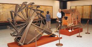 米作りの四季を描いたびょうぶと、町内で使われていた農具=愛荘町立歴史博物館で