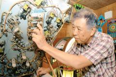 ゲーム機の裏側の配線を点検する和田員昌さん=熱海市昭和町で