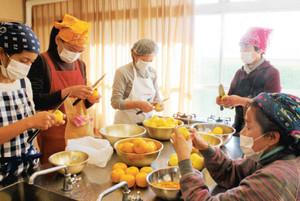 サトイモ田楽のみそに使うユズの皮を切る女性たち=南砺市院林で