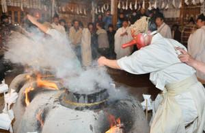 煮えたぎる湯を素手で払う「湯切り」=飯田市上村上町の上町正八幡宮で