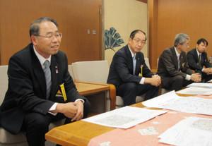 金沢周遊バスの逆回りルート運行を報告する北陸鉄道の加藤社長(左)=金沢市役所で
