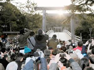 大勢の参拝者が見守る中、宇治橋の中央から昇る冬至の朝日=昨年12月、三重県伊勢市の伊勢神宮内宮前で