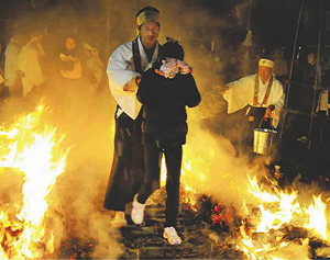 熱さと煙に耐えながら火渡り場を歩く参拝者=昨年、愛知県小牧市大草の福厳寺で