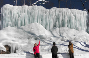 巨大な氷柱を眺める人たち=高山市清見町の彦谷の里で