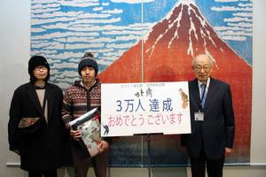 3万人目となり、馬場駿吉館長(右)から記念品を受けた水野功さん(中)と池田由紀子さん=名古屋・金山の名古屋ボストン美術館で