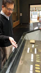 旧家から発見された小判などの貨幣について説明する中島誠一館長=長浜市の曳山博物館で