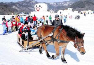 大きな雪だるまが登場した会場で馬ぞりを楽しむ来場者ら=木曽町開田高原で