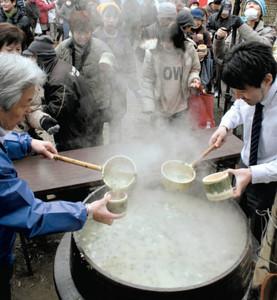 大釜で炊いた七草がゆを求める参加者=昨年2月、三重県松阪市柚原町で