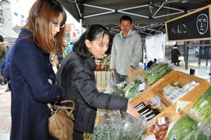 地産の食材や加工品を手に取る客ら=伊賀市の伊賀鉄道上野市駅前広場で