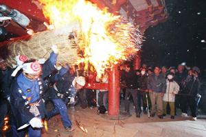点火されたたいまつを担いで駆ける男たち=昨年3月、愛知県津島市の津島神社で