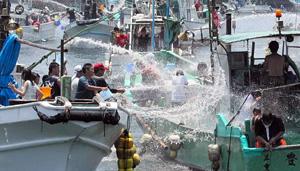 豊漁と安全を願い、ホースやバケツで海水を掛け合う漁船=昨年、三重県志摩市の和具漁港で