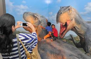 恐竜の背に乗ったように見えるトリックアートを楽しむ来場者=名古屋・名駅の名鉄百貨店で