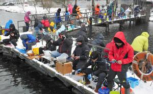 雪が舞う中、ワカサギ釣りを楽しむ人たち=長浜市余呉町で