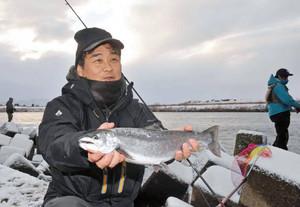 釣ったサクラマスを手に笑顔の大谷尚之さん=福井市の九頭竜川高屋橋上流で