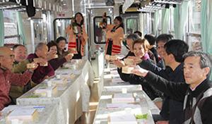 枡酒列車の車中で乾杯する参加者たち=恵那市で