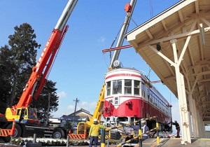 クレーンでプラットホームに移される赤白電車=大野町の黒野駅レールパークで