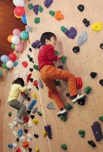 ブロックに手足をかけて壁を登る子どもたち=瑞浪市釜戸町の市自然ふれあい館で