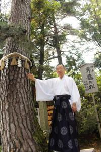 昇龍道にそびえる昇龍の松を紹介する上田正浩宮司=小松市浜田町で