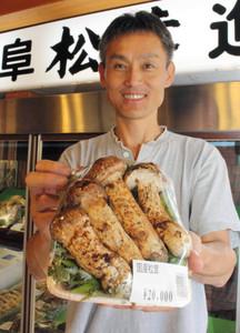 見事な県産マツタケを手にする加藤博信代表=山県市佐賀のマルキクで