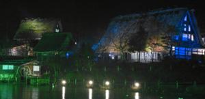 ライトアップで幻想的に浮かび上がる合掌造り家屋=高山市上岡本町の飛騨の里で