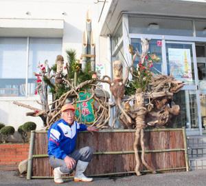 来年のえとのさるなどをかたどった木彫り作品と門松を仕上げた川畑良輔さん=福井市鮎川町の国見公民館前で