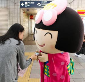 通勤客に自らの名刺を手渡す梅子=名鉄朝倉駅で