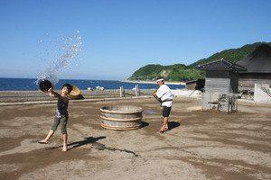 塩田で潮まきをする道下翔太君(左)と登谷良一さん