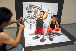 作品パネルの上でポーズを取り、写真を撮ってもらう子どもたち=美濃市蕨生の美濃和紙の里会館で