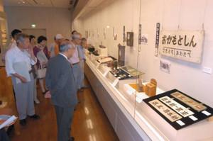 福井鉄道南越線で使われていた駅の看板などを見学する来場者=越前市の武生公会堂記念館で