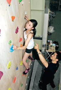集中して壁を登っていく女性(左)とサポートするジムの金子謹也代表=小松市南浅井町で