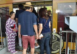 かごをデザインしたゴンドラの前で、利用者を案内する和装の女性ガイド(左)=静岡市駿河区で
