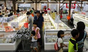 生鮮食品や干物が並び、親子らでにぎわうおわせお魚いちばおとと=尾鷲市古戸野町で