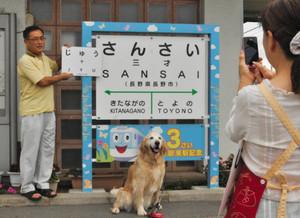 年齢看板を使って愛犬と記念撮影する家族連れ=長野市のJR三才駅で