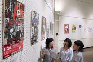 「BIG APPLE in Nonoichi」の歴代ポスターを懐かしそうに眺める女性たち=野々市市文化会館フォルテで