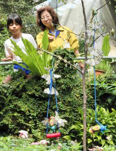 オオゴマダラと戯れるこびとのキャラクターのフィギュアを探す児童たち=県ふれあい昆虫館で