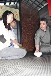 アルミや銅板、漆器でつくった茶室でお茶を楽しむ来場者=いずれも高岡市御旅屋町で
