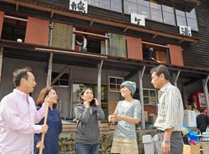 清掃ボランティアに訪れた若者たちと談笑する中島尋幸マネジャー(右)=大野市の鳩ケ湯で