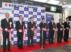 テープカットで中部-羽田便の就航を祝う関係者ら=中部国際空港で