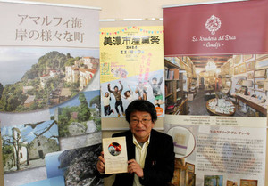 美濃、アマルフィ両市の文化を紹介する冊子を手に産業祭をPRする担当者の高木宏和さん=美濃市生櫛の市教委で