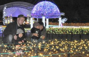 音楽に合わせて輝くイルミネーションを楽しむ家族連れ=佐久市内で