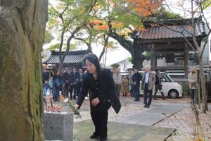 墓碑に献花して徳田秋声を追悼する参列者たち=金沢市材木町の静明寺で