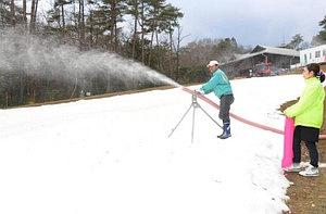 砕いた氷を噴射する造雪機で人工雪のゲレンデを整備する職員ら=豊田市旭八幡町の「旭高原元気村」で