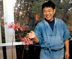 銅でつくったヒガンバナと彫金作家の河合隆男さん=沼津市我入道で