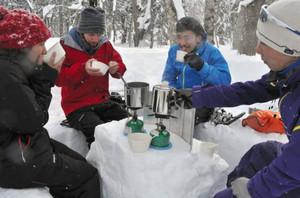 雪で作ったテーブルを囲み、スープやコーヒーで体を温める参加者ら=長野市内で