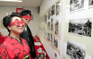 赤いちょうちんの形をした「大須めがね」をかけて商店街の古い写真を見る人たち=名古屋市中区で