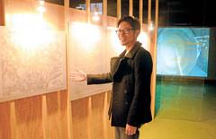 豆腐を作る工程を収めた映像作品や戦時中の浜松の地図を説明する大東さん=浜松市中区の旧文泉堂書店で