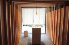 豆腐店を意識したのれんと木枠に囲まれた展示スペースの入り口